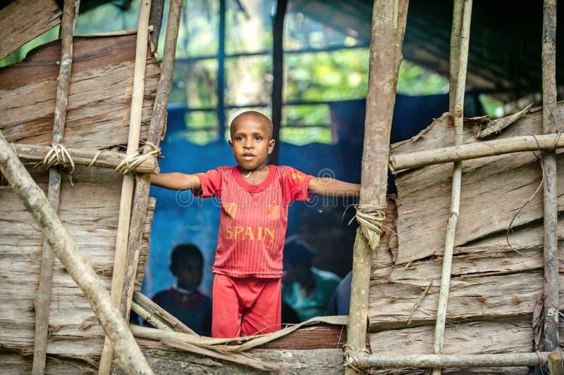 Retrato de rapaz pequeno não identificado do Papuan no vermelho foto de stock