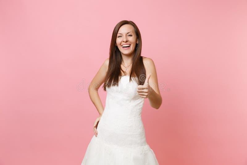 Retrato de reír a la mujer alegre de la novia en la situación blanca elegante del vestido que se casa y de mostrar el pulgar para imagen de archivo libre de regalías