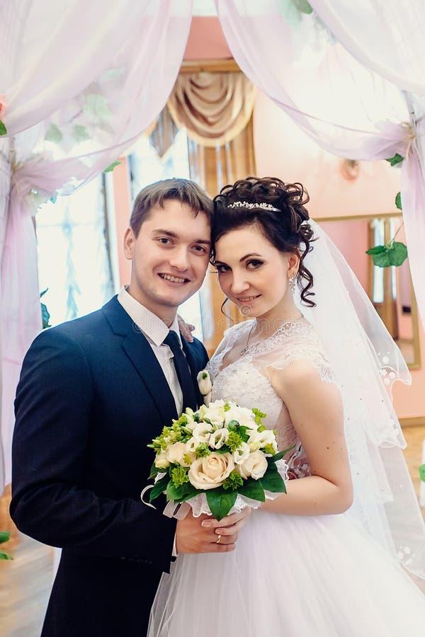 Retrato de recienes casados felices en el pasillo que se casa imagen de archivo