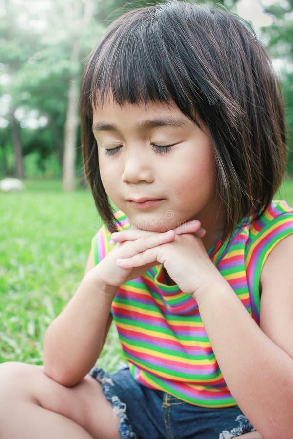 Retrato de rezar asiático novo pequeno da menina fotografia de stock