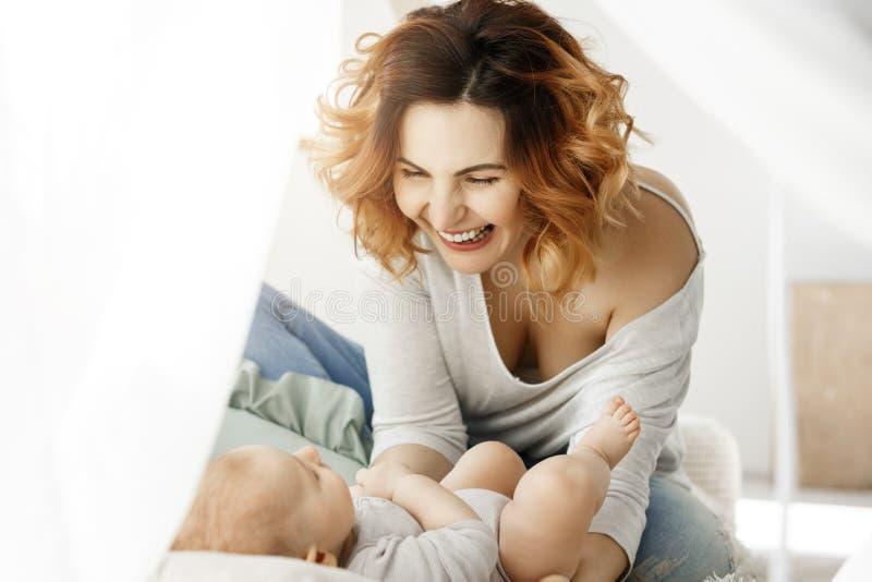Retrato de risos atrativos novos e do jogo da mãe com a criança recém-nascida no quarto claro confortável Manhãs mornas com imagem de stock