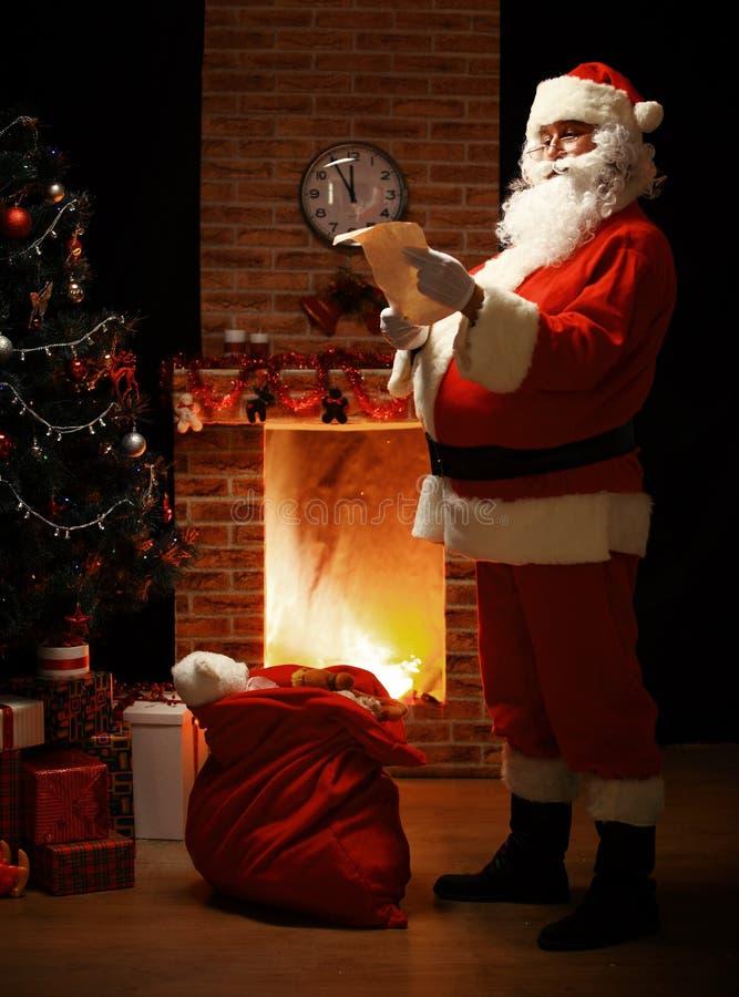 Retrato de Santa Claus feliz que se coloca en su sitio en casa imagen de archivo