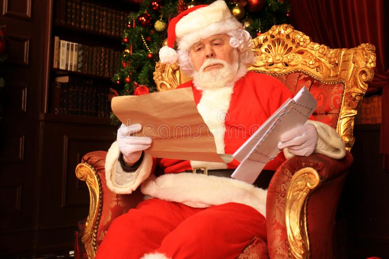 Retrato de Santa Claus feliz que senta-se em sua sala em casa perto da árvore de Natal e que lê a letra ou a lista de objetivos p fotos de stock