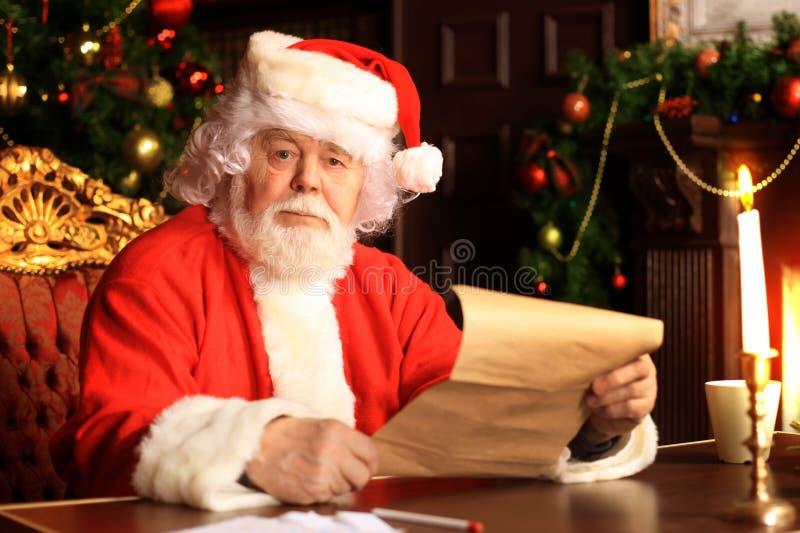 Retrato de Santa Claus feliz que senta-se em sua sala em casa perto da árvore de Natal e que lê a letra ou a lista de objetivos p fotografia de stock royalty free