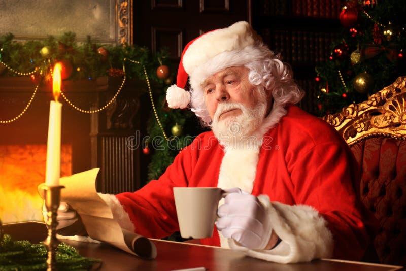Retrato de Santa Claus feliz que senta-se em sua sala em casa perto da árvore de Natal e que lê a letra ou a lista de objetivos p imagens de stock