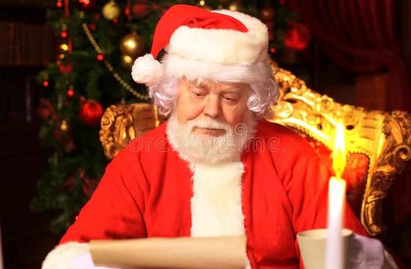 Retrato de Santa Claus feliz que senta-se em sua sala em casa perto da árvore de Natal e que lê a letra ou a lista de objetivos p fotos de stock royalty free