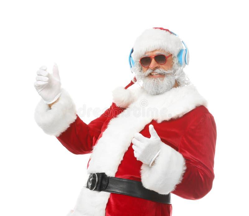 Retrato de Santa Claus que escucha la música y que baila en el fondo blanco fotografía de archivo