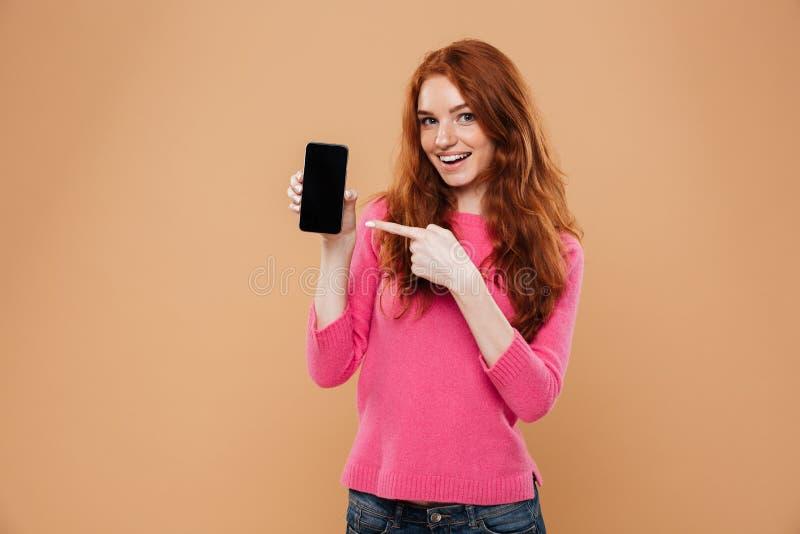 Retrato de señalar atractivo emocionado de la muchacha del pelirrojo imagen de archivo libre de regalías