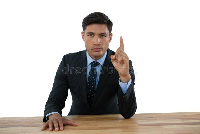 Retrato de señalar confiado del hombre de negocios ascendente mientras que se sienta en la tabla fotos de archivo libres de regalías