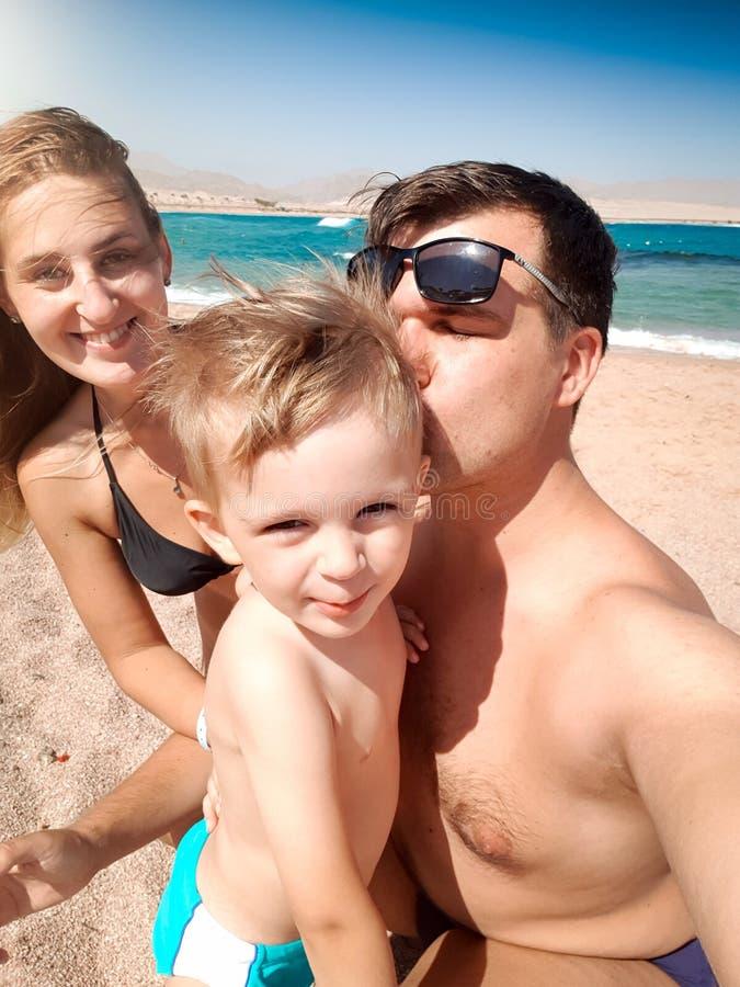 Retrato de Selfie dos pais que beijam o filho pequeno da criança na praia do mar no dia ventoso ensolarado Família que relaxa e q fotos de stock royalty free