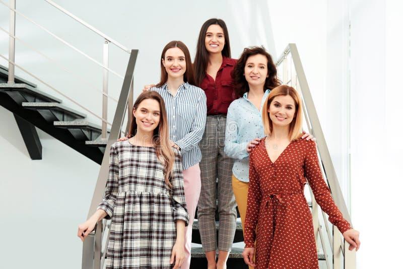 Retrato de senhoras felizes em escadas conceito do poder das mulheres foto de stock royalty free