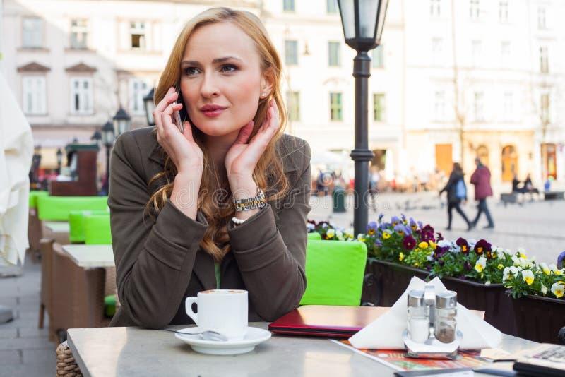 Retrato de sentarse lindo joven de la mujer elegante al aire libre en un café i foto de archivo