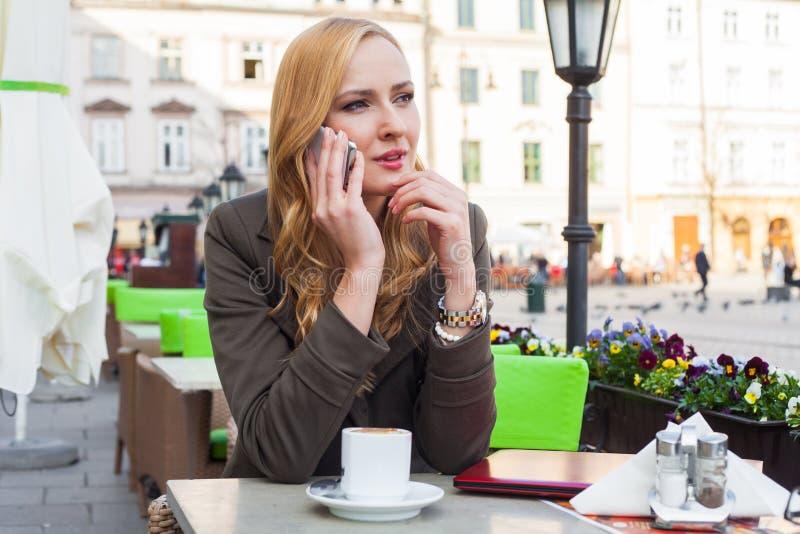 Retrato de sentarse lindo joven de la mujer elegante al aire libre en un café i imagen de archivo libre de regalías