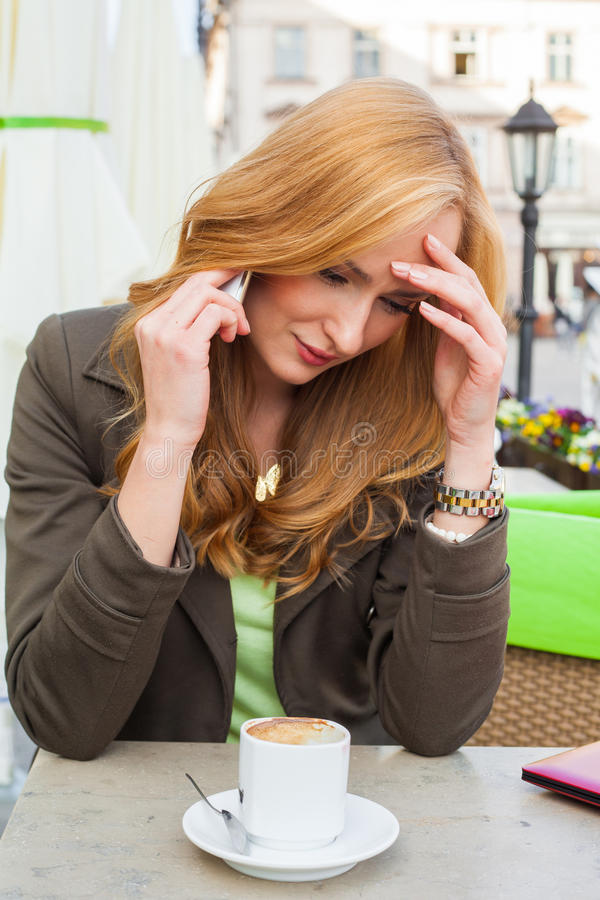 Retrato de sentarse lindo joven de la mujer elegante al aire libre en un café i fotografía de archivo libre de regalías