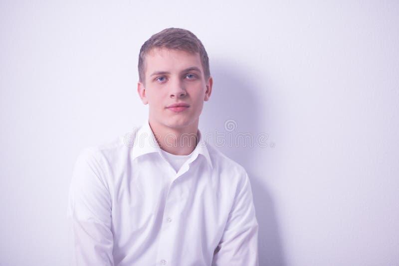 Retrato de sentarse sonriente del hombre joven en fondo gris Retrato del hombre joven foto de archivo