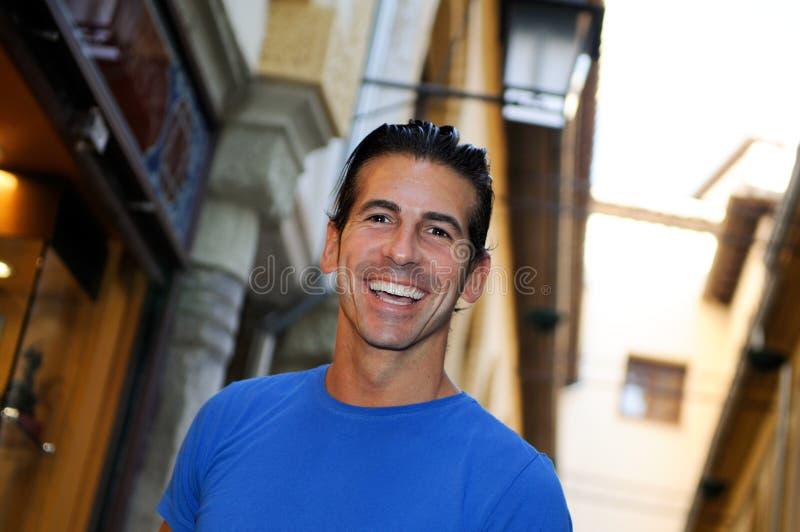 Retrato de sorriso atrativo do homem no fundo urbano fotografia de stock
