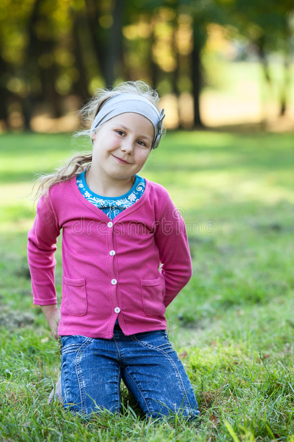 Retrato de sorriso bonito da menina, estando em genuflexões na grama fotografia de stock royalty free