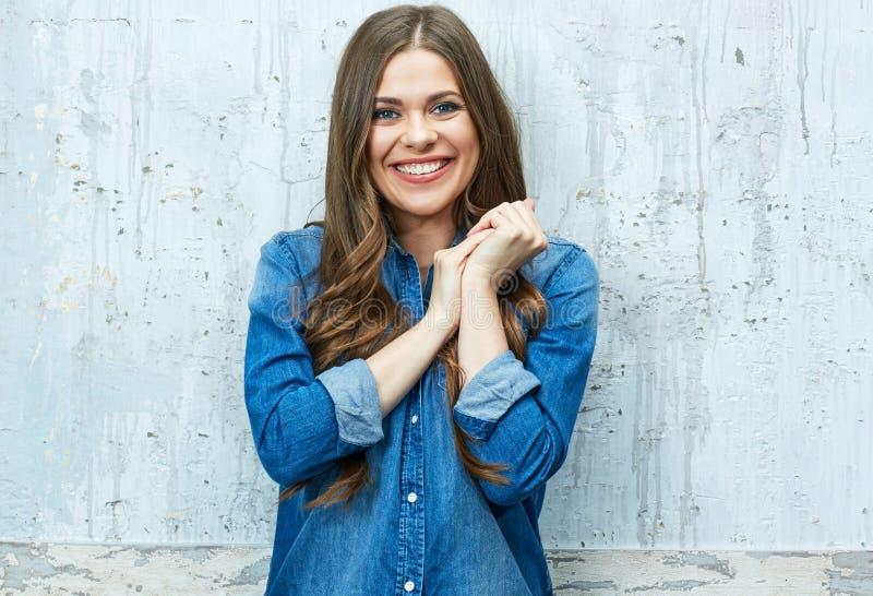 Retrato de sorriso da jovem mulher contra a parede cinzenta fotos de stock