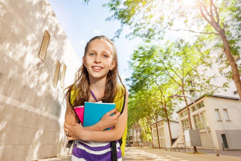 Retrato de sorriso de uma menina agradável com livros de texto imagem de stock royalty free