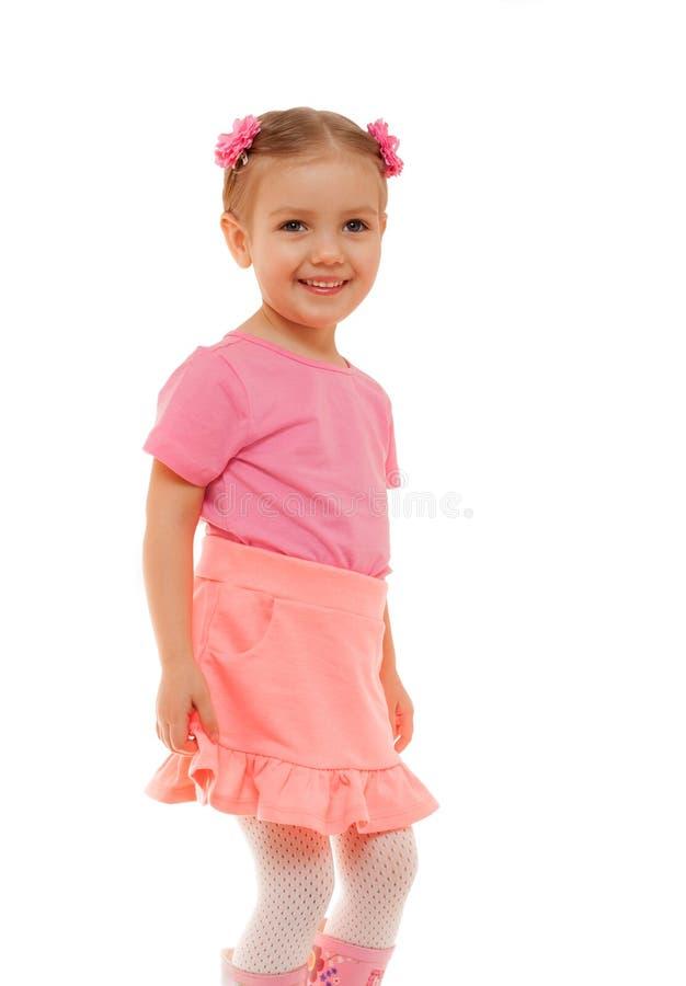 Retrato de sorriso do estúdio da cara do divertimento da saia do t-shirt do rosa da menina da criança foto de stock royalty free