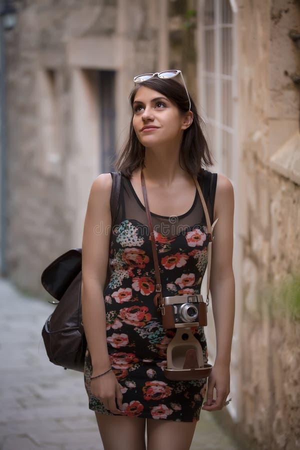Retrato de sorriso do estilo de vida do verão exterior da jovem mulher bonita que tem o divertimento na cidade em Europa com a câ imagem de stock