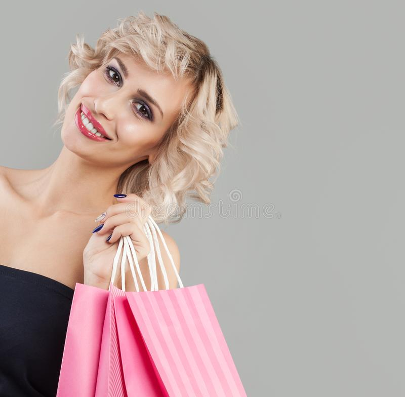 Retrato de sorriso feliz da mulher Modelo bonito com sacos de compras cor-de-rosa foto de stock royalty free