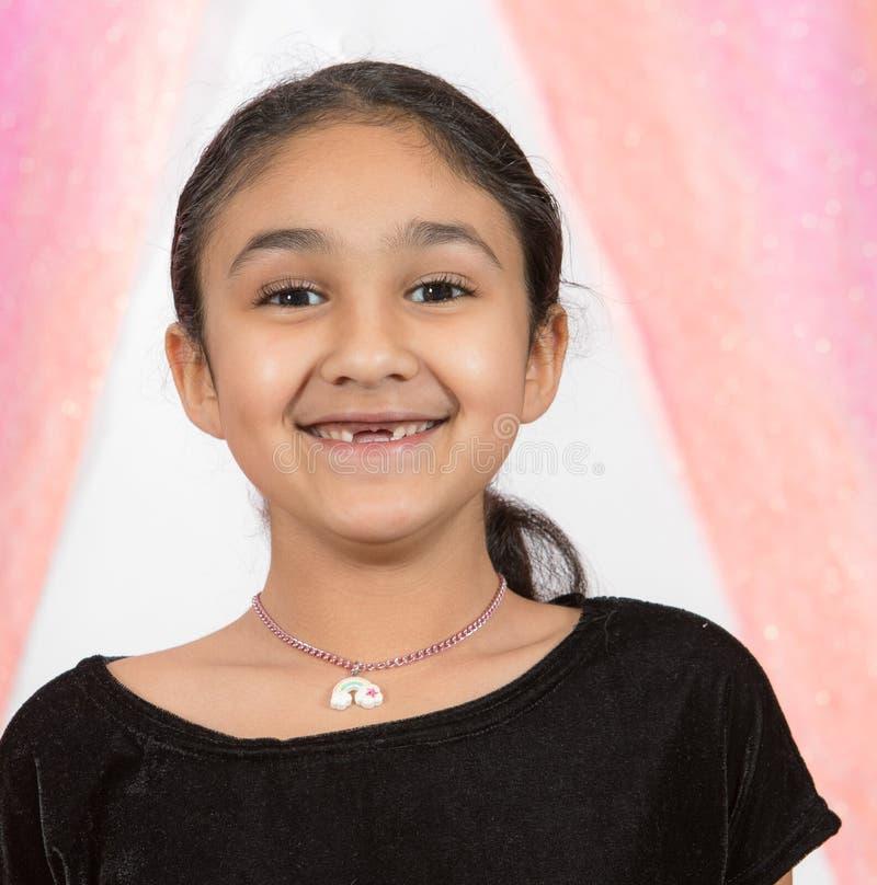 Retrato de sorriso de uma menina com os dentes de bebê de falta fotografia de stock royalty free