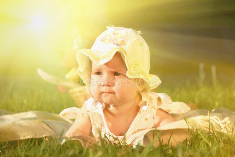 Retrato de surpreender a menina adorável da criança que descansa na grama sobre fotografia de stock