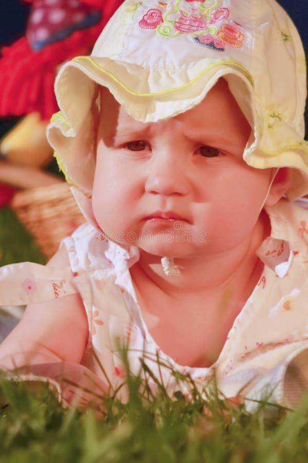 Retrato de surpreender a menina ador?vel da crian?a que descansa na grama sobre foto de stock royalty free