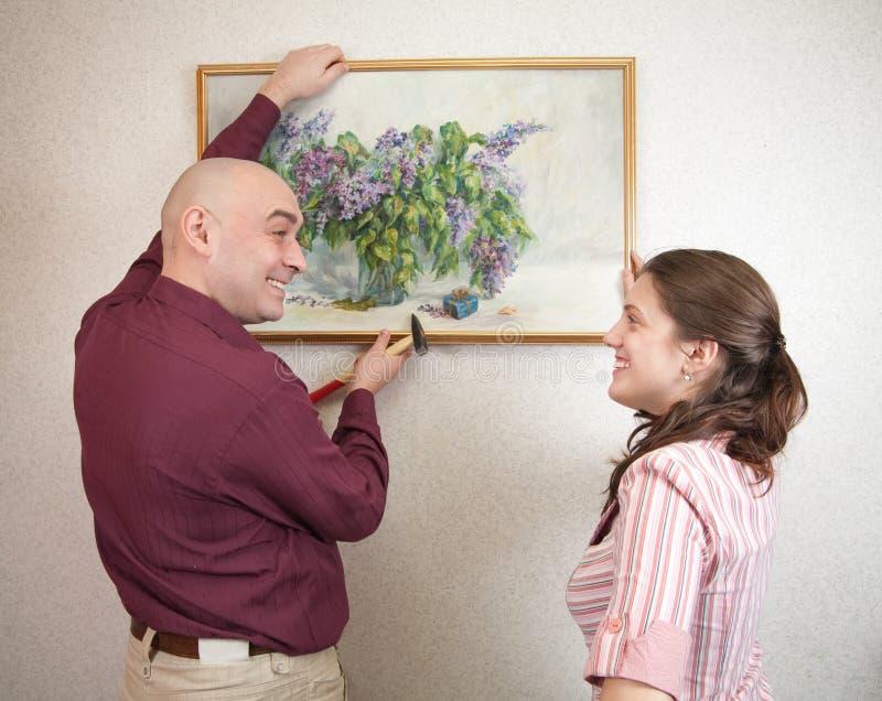 Retrato de suspensão da arte dos pares novos na parede em fotografia de stock