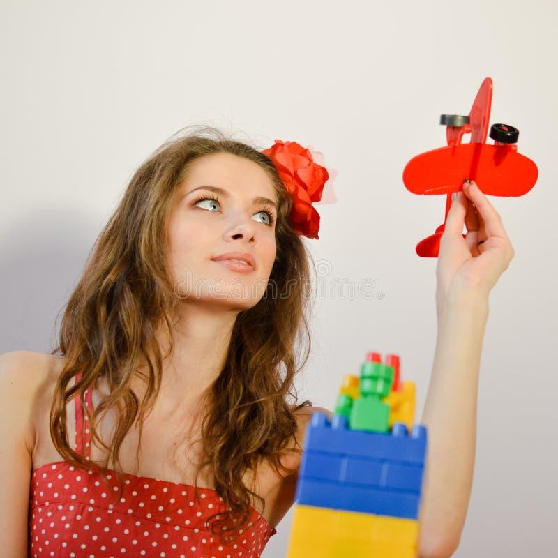 Retrato de ter o divertimento que joga com a jovem senhora engraçada bonita do avião do brinquedo no vestido do às bolinhas que o fotografia de stock royalty free
