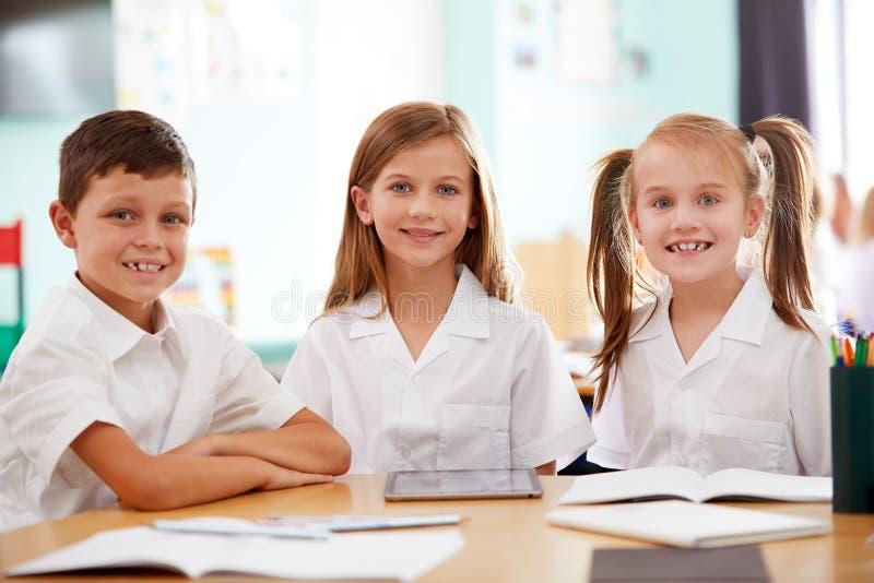 Retrato de três alunos da escola primária que vestem a tabuleta de utilização uniforme de Digitas na mesa imagem de stock royalty free