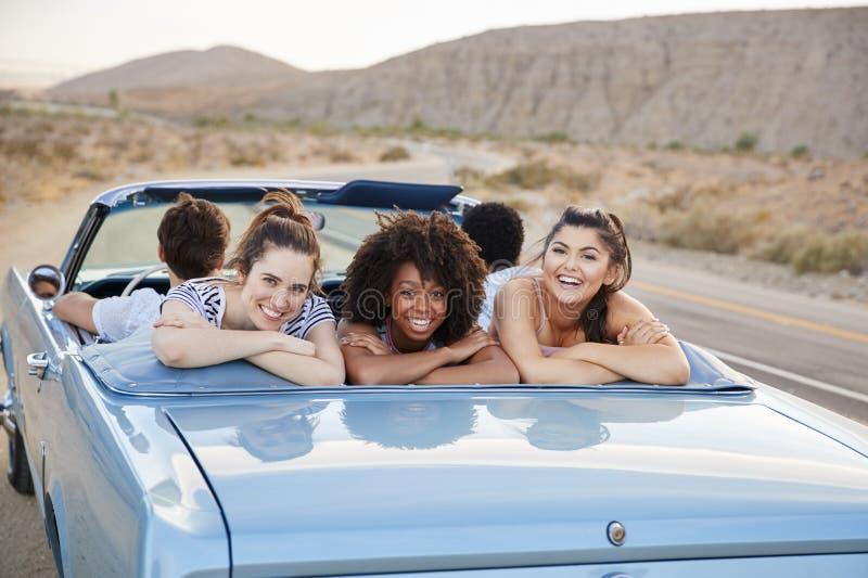 Retrato de três amigos fêmeas que apreciam a viagem por estrada no carro clássico superior aberto fotografia de stock