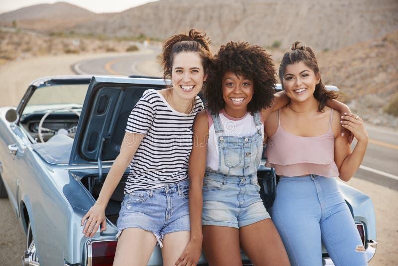 Retrato de três amigos fêmeas que sentam-se no tronco do carro clássico na viagem por estrada imagens de stock