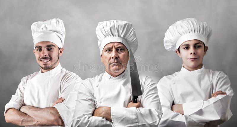 Retrato de três cozinheiros chefe fotografia de stock