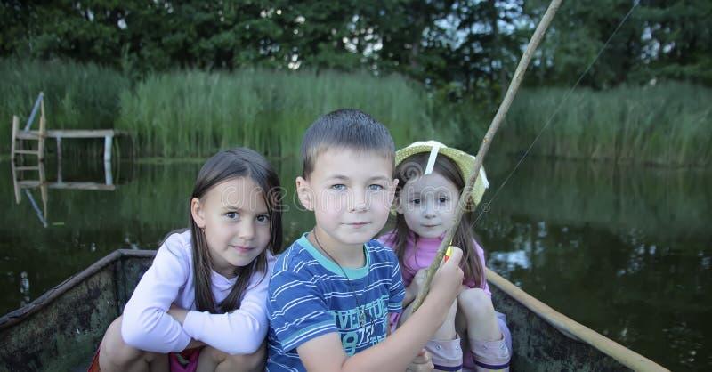 Retrato de três crianças que pescam em um barco fotos de stock