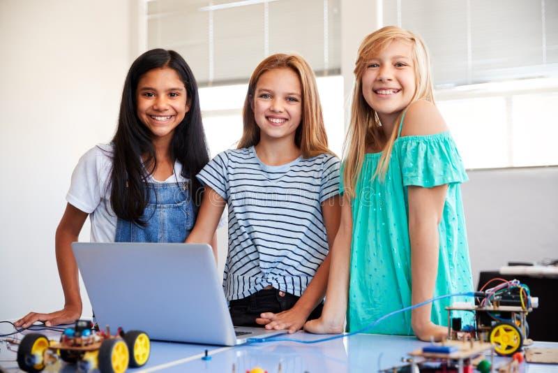 Retrato de três estudantes fêmeas que constroem e que programam o veículo do robô na classe do computador da escola imagem de stock royalty free