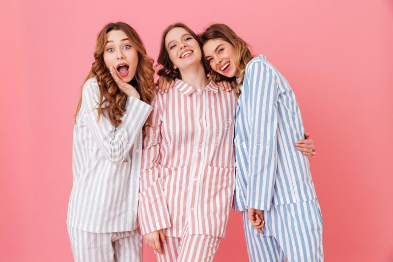 Retrato de três moças bonitas 20s que vestem o estreptococo colorido fotos de stock