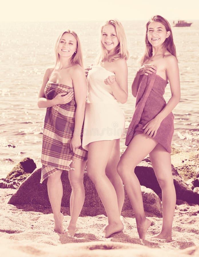 Retrato de três mulheres alegres envolvidas nas toalhas imagem de stock royalty free