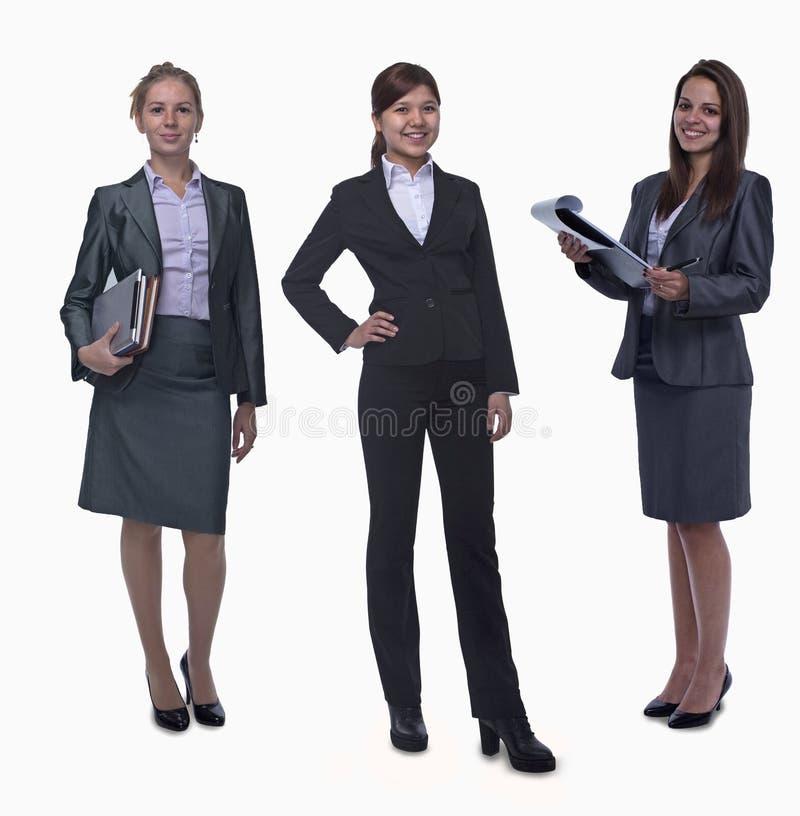 Retrato de três mulheres de negócios de sorriso novas, olhando a câmera, tiro do estúdio imagens de stock royalty free