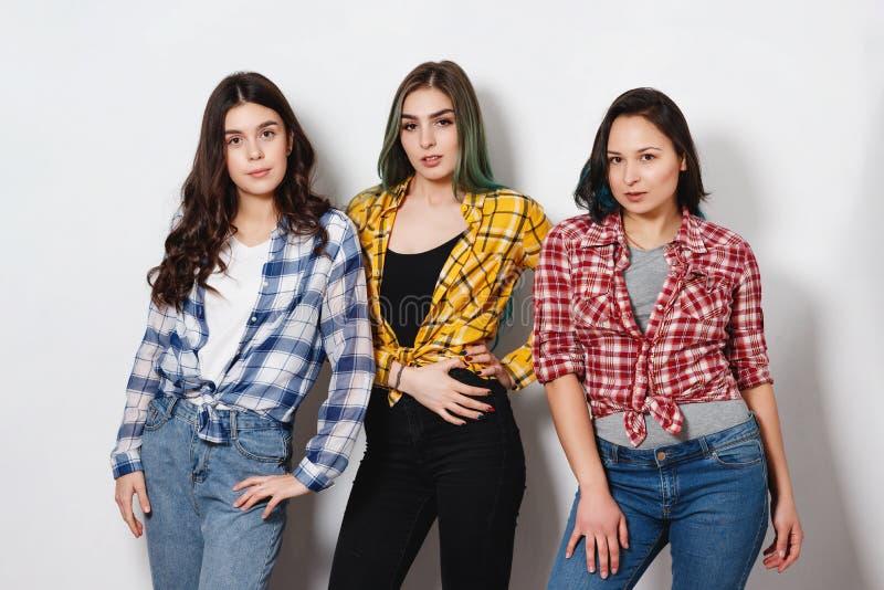 Retrato de três mulheres delgadas bonitas novas das meninas nas camisas de manta vermelhas, amarelas e azuis no fundo branco fotografia de stock royalty free
