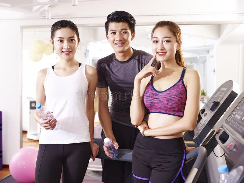 Retrato de três povos asiáticos novos no gym fotos de stock royalty free