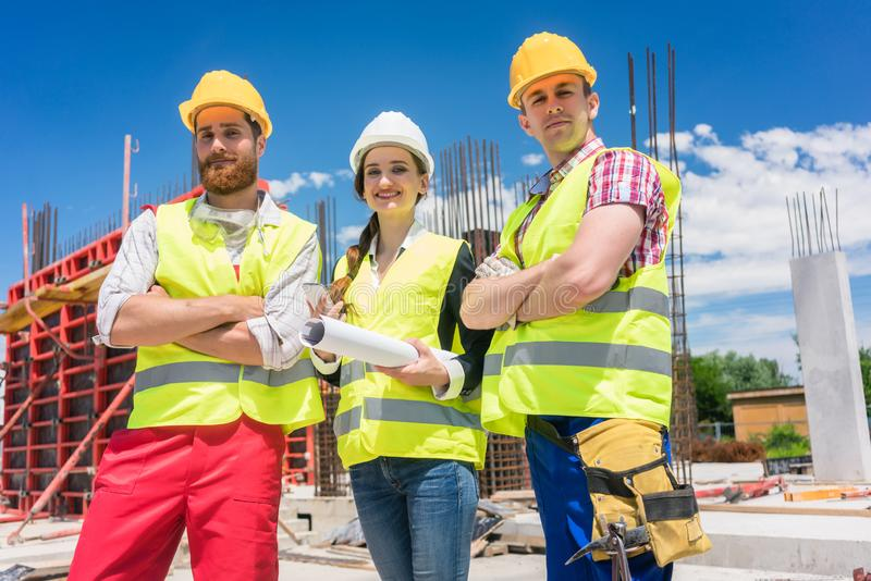 Retrato de três seguros e empregados novos seguros no canteiro de obras foto de stock