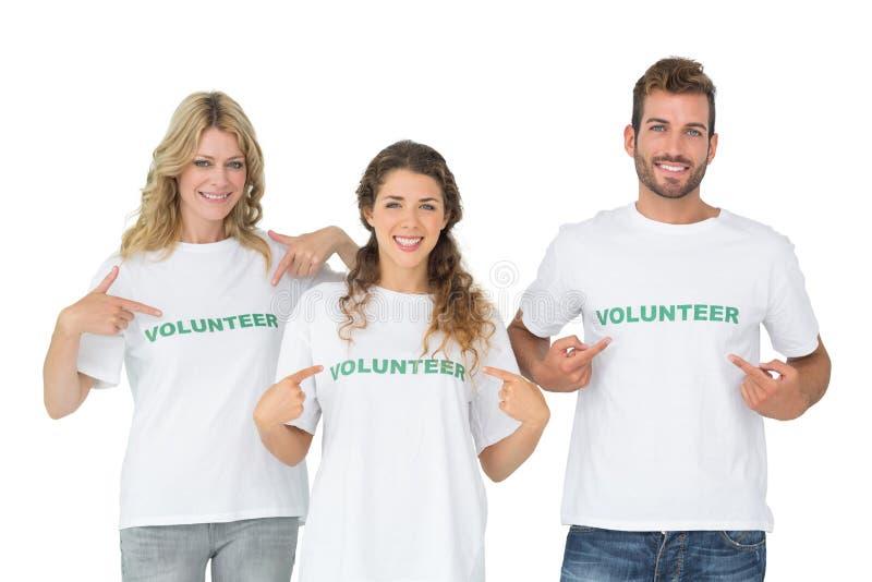 Retrato de três voluntários felizes que apontam a se imagens de stock royalty free
