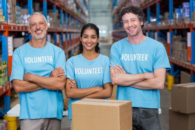 Retrato de três voluntários felizes que estão com os braços cruzados imagens de stock