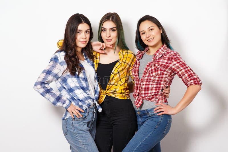 Retrato de tr?s mulheres delgadas bonitas novas das meninas nas camisas de manta vermelhas, amarelas e azuis no fundo branco imagens de stock royalty free