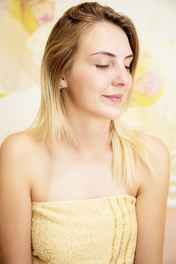 Retrato de tratamentos de espera de sorriso ou de cosmetologist dos termas da menina loura bonita foto de stock