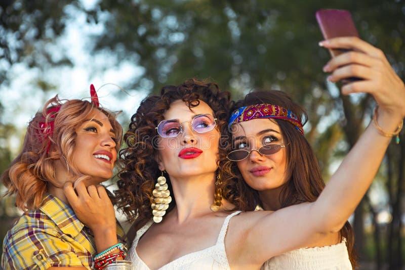 Retrato de tres amigos que toman las fotos con un smartphone foto de archivo libre de regalías