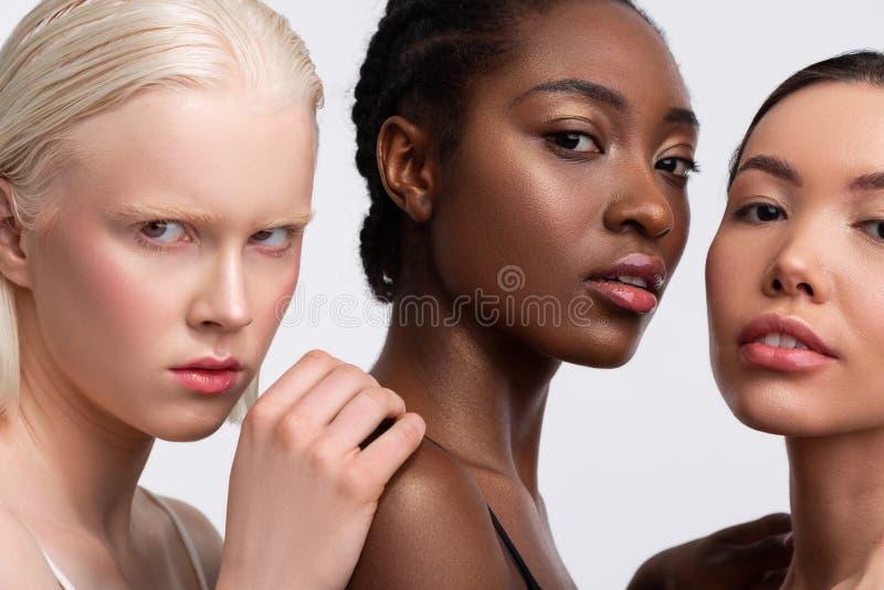 Retrato de tres hembras con diversa sensaci?n de la tez confiada foto de archivo