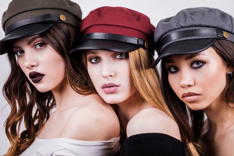 Retrato de tres hermosos, de mujeres atractivas, de novias con maquillaje y del casquillo colorido, sombreros en su cabeza, cierr fotografía de archivo libre de regalías
